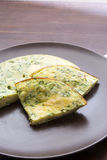 Omelet with spinach and zucchini with melted cheese on brown pla Royalty Free Stock Images