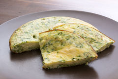 Omelet with spinach and zucchini with melted cheese on brown pla Stock Photography