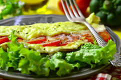 Omelet stuffed with tomatoes and cheese. Stock Photography