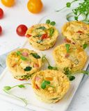 Omelet with tomatoes and bacon, baked eggs with spinach and broccoli, closeup, vertical, keto, ketogenic diet.  stock photo