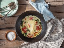Omelet with tomatoes and spinach in a round cast iron pan on an old Board table, cotton napkins and coarse salt in a. Breakfast omelet with tomatoes and spinach royalty free stock photos