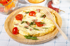 Omelet with tomatoes on wooden plate. Scrambled eggs with tomatoes on plate Stock Images