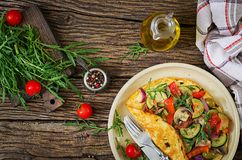 Omelet with tomatoes, zucchini and mushrooms. Omelette breakfast. Healthy food. Top view. Flat lay stock photo
