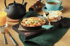 Omelet with vegetables and cheese. Frittata in a frying pan^ breakfast set stock photos