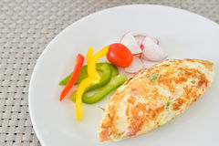 Omelet with vegetables on white plate Stock Photos