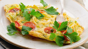 Omelet with vegetables in a white plate. Royalty Free Stock Photo