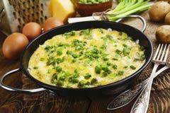 Omeleta com ervilhas verdes, batatas e queijo imagens de stock
