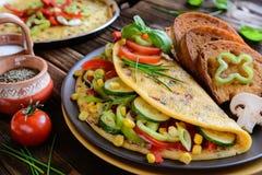Omeleta com pimenta, tomate, milho, a cebola verde, o pepino, os cogumelos e pão fritado Fotografia de Stock Royalty Free
