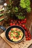 Omeleta com presunto, tomates e chees na frigideira Foto de Stock