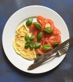 A omeleta com salada e manjericão do tomate sae na placa Foto de Stock Royalty Free