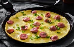 Omeleta com salsicha em uma frigideira na tabela de madeira Imagem de Stock