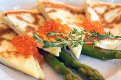 Omeleta cortada com fim vermelho do caviar acima foto de stock
