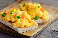 Omeleta dos ovos mexidos A omeleta caseiro dos ovos mexidos com os vegetais no pão friável brinda Comer saudável Estilo rústico imagens de stock royalty free