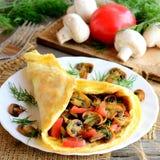 Omeleta enchida em uma placa Omeleta caseiro com fatias dos cogumelos, tomates e aneto em uma placa, ingredientes, forquilha foto de stock