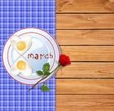 Omeleta na placa com ketchup letras do 8 de março e na rosa do vermelho em w Imagens de Stock