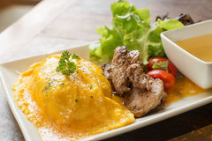Omelete rice with grilled pork. Omelete rice with roasted pork on wood table stock photo
