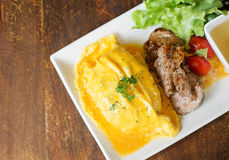 Omelete rice with roasted pork. On wood table Royalty Free Stock Photos