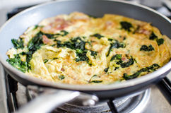 Omelete. With spinach on frying pan royalty free stock image