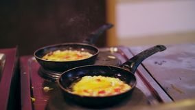 Omelets, fried eggs, cooked on the stove in two greasy, dirty, pans. stove is dirty too. over the pans you can see a. Light smoke stock video