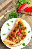 Omelett för välfyllt ägg med grönsaker på en platta Lätt äggrecept Top beskådar royaltyfri foto