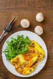 Omelett med champinjoner och arugulasallad i den vita plattan på trätabellen royaltyfri foto