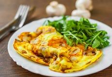 Omelett med champinjoner och arugulasallad i den vita plattan på trätabellen royaltyfria bilder
