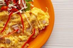 Omelett med den gröna och röda grönsaken och ost för frukost i en platta på trätabellen arkivbilder