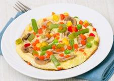 Omelett med grönsaker och champinjoner royaltyfria foton