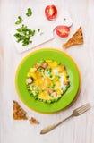 Omelett med gröna ärtor, potatisar och korvar som tjänar som med tomater, persilja och rostat bröd Arkivfoto