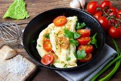 Omelett med körsbärsröda tomater och ny grön persilja i en svart järnpanna royaltyfria foton