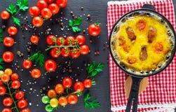 Omelett med korvar och hönaägg i en rund järn- kruka royaltyfria foton