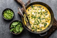 Omelett med spenat och ost i en bästa sikt för panna arkivfoton