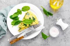 Omelett med spenatsidor Omelett på plattan, förvanskade ägg arkivfoto