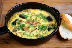 Omelett mit dem Gemüse, besprüht mit Kräutern, in einer Bratpfanne und in zwei Scheiben brot auf einem Holztisch Stockbilder