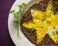 Omelett mit dem Vollweizenbrot und -petersilie sternförmig auf purpurroter Tischdecke Stockfoto