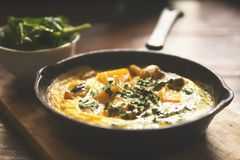 Omelett mit Gemüse in der alten Weinlese-Eisen-Bratpfanne auf Holztisch Autumn Vegetarian Breakfast Lizenzfreie Stockfotografie