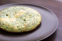 Omelett mit Spinat und Zucchini mit geschmolzenem Käse auf braunem Winkel des Leistungshebels Stockbild