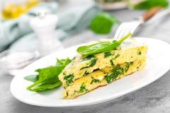 Omelett mit Spinatsblättern Omelett auf Platte, durcheinandergemischte Eier Lizenzfreies Stockfoto