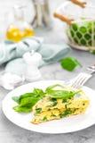 Omelett mit Spinatsblättern Omelett auf Platte, durcheinandergemischte Eier Lizenzfreies Stockbild