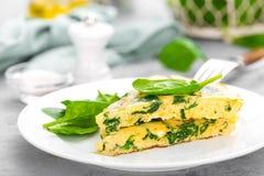 Omelett mit Spinatsblättern Omelett auf Platte, durcheinandergemischte Eier Lizenzfreie Stockbilder