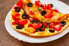Omelett mit Tomate, Pfeffer und Olive in der weißen Platte auf Holztisch lizenzfreie stockfotografie
