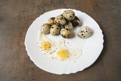 Omelett- och vaktelägg på en vit platta Arkivbild