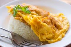 Omelett på ris, mat, ris, guling, gaffel och skeden Royaltyfri Foto