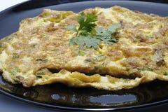 Omelett som stekas på svart maträtt Royaltyfri Foto