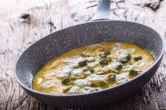 Omelett von den Eiern Spargel und Käse in der keramischen Wanne auf altem eichenem Tisch Stockfotografie