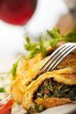 Omelette. Slices of spinach omelette with wine Royalty Free Stock Images