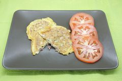 Omelette. Stuffed with diced prosciutto accompanied by three slices of fresh tomato royalty free stock photo