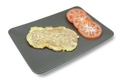 Omelette. Stuffed with diced prosciutto accompanied by three slices of fresh tomato stock image