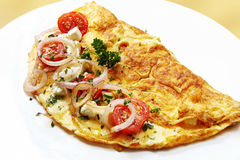 Omelette. With cherry tomatoes, red onion, mozzarella, goat's cheese and herbs.  A delicious, nutritious breakfast Stock Images