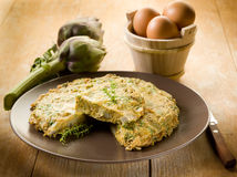 Omelette with artichokes. On wood background Royalty Free Stock Image
